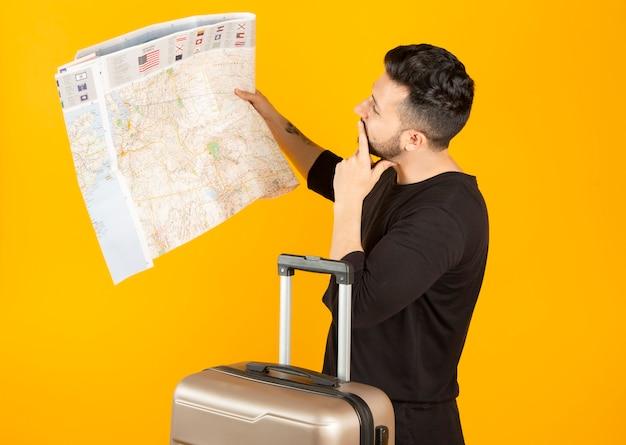 Uomo con un concetto di viaggio mappa e valigia,