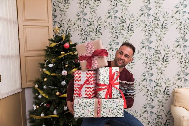 Uomo con un mucchio di regali vicino all'albero di natale