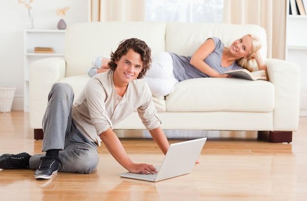 Uomo con un notebook mentre la sua ragazza è con un libro
