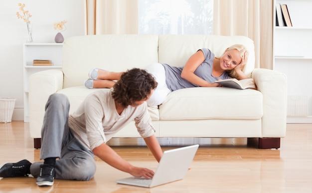 Uomo con un portatile mentre la sua ragazza è in possesso di un libro