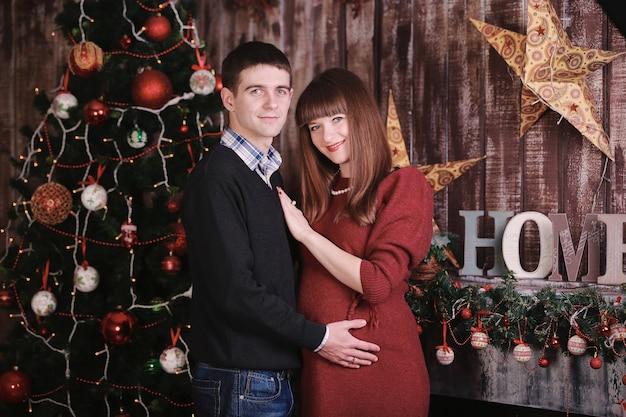 Uomo con una donna incinta che posa vicino all'albero di natale