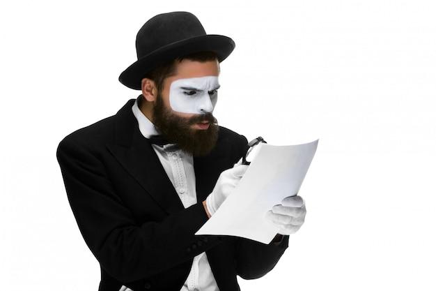 Uomo con una faccia mime lettura attraverso la lente di ingrandimento