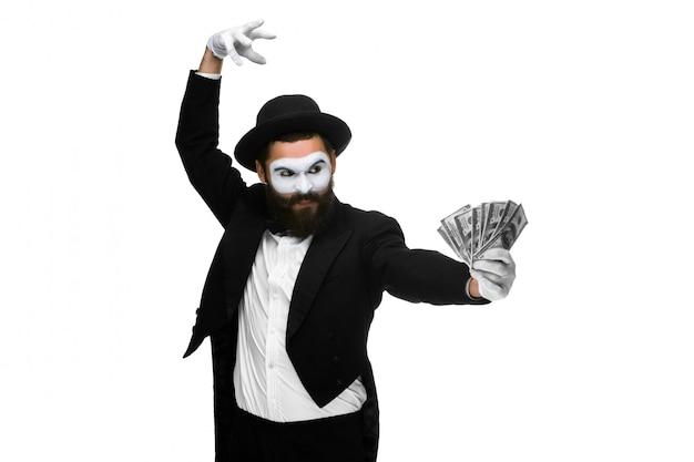 Uomo con una faccia mimo ballando con denaro isolato su un concetto bianco concetto di amore per i soldi, la felicità dalla fortuna dei soldi