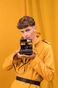 Uomo con una fotocamera retrò in una scena gialla