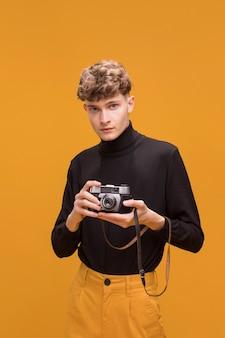 Uomo con una macchina fotografica in una scena gialla