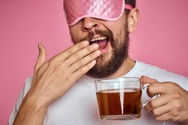 Uomo con una maschera per dormire e con in mano una tazza di tè