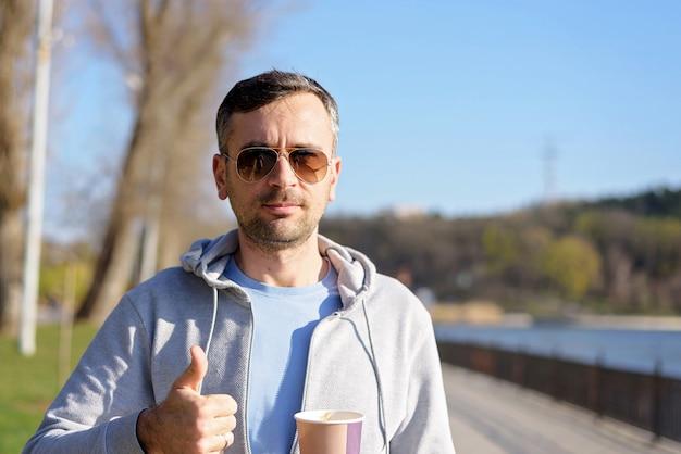 Uomo con una tazza di caffè e un pollice in su