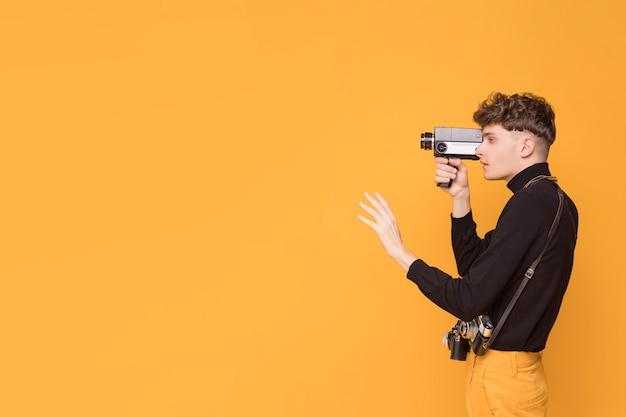 Uomo con una videocamera in una scena gialla