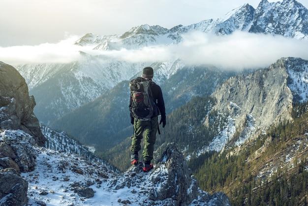 Uomo con uno zaino in piedi sulla cima della montagna