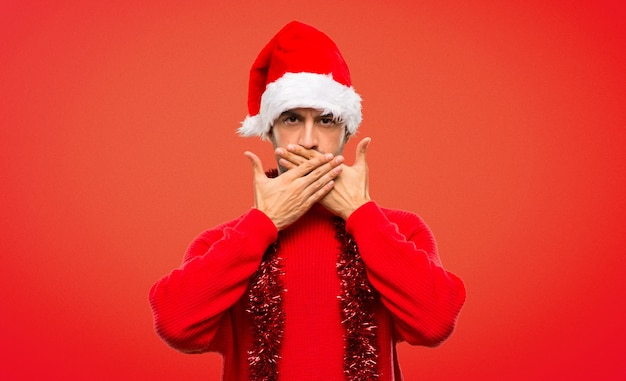 Uomo con vestiti rossi che celebra le feste di natale che coprono la bocca con le mani