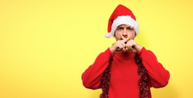 Uomo con vestiti rossi che celebrano le vacanze di natale mostrando un segno di silenzio gesto