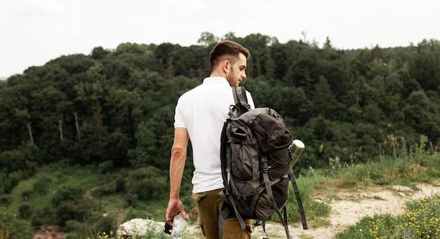Uomo con zaino in viaggio nella foresta