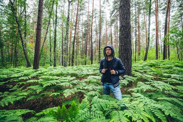 Uomo con zaino nella foresta.