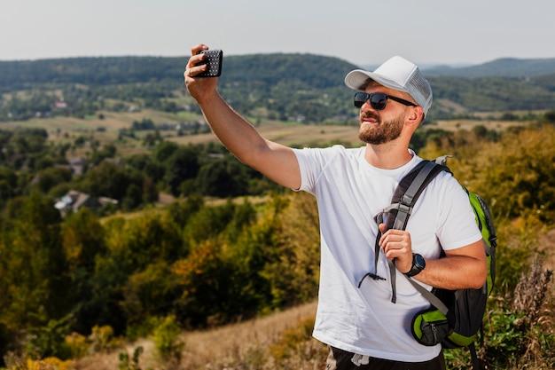 Uomo con zaino prendendo selfie