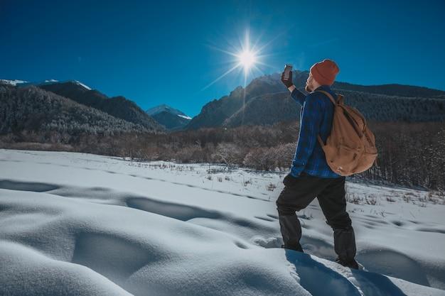 Uomo con zaino trekking in montagna. freddo, neve sulle colline. escursioni invernali. sole e neve