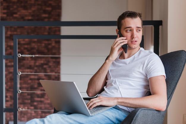 Uomo concentrato che parla sul telefono cellulare e che si siede sulla sedia con il computer portatile