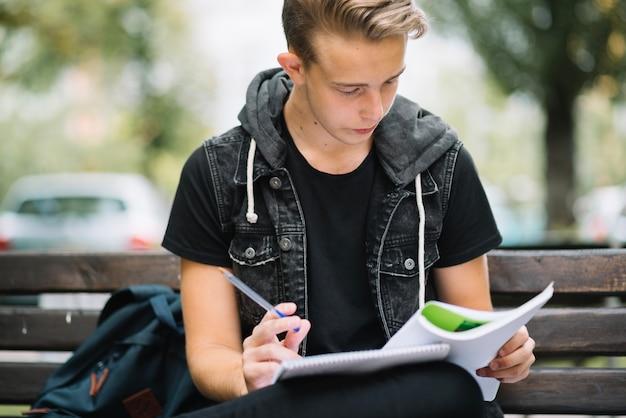 Uomo concentrato che studia all'esterno
