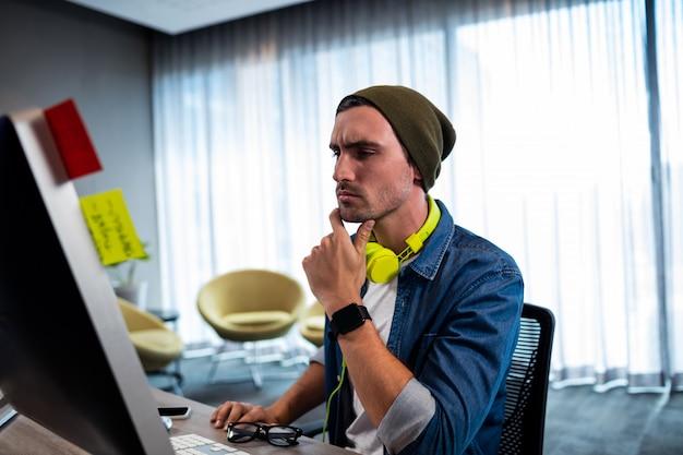 Uomo concentrato dei pantaloni a vita bassa che lavora con l'auricolare audio