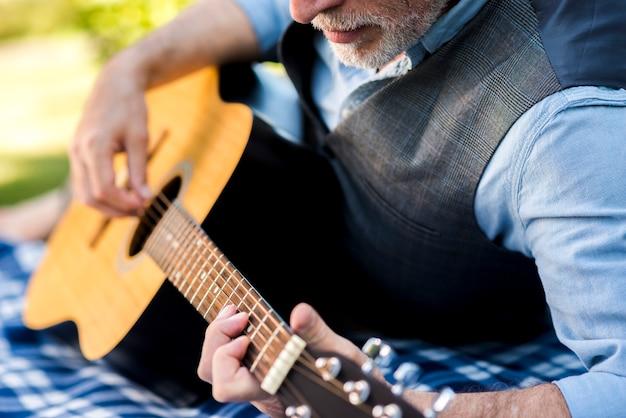 Uomo concentrato di vista vicina che gioca chitarra