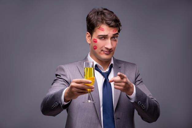 Uomo coperto da baci con un bicchiere di champagne