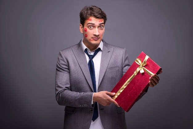 Uomo coperto di baci con regalo