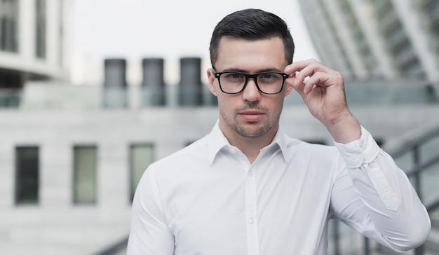 Uomo corporativo che propone con gli occhiali