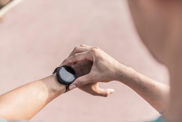 Uomo corrente che guarda orologio sportivo. maschio che fa jogging usando l'orologio intelligente all'esterno