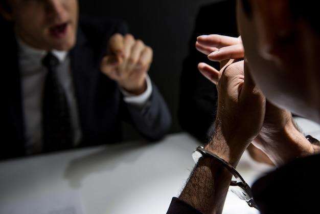Uomo criminale con le manette che sono intervistate nella stanza di interrogatorio