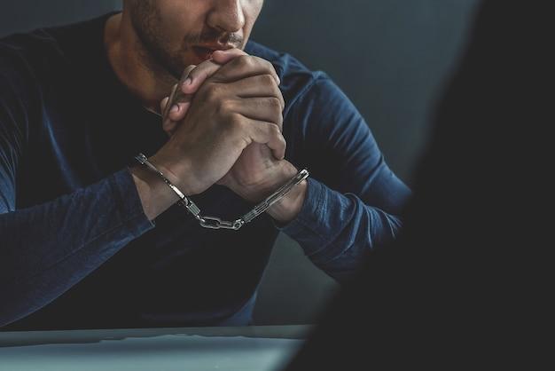 Uomo criminale con le manette nella stanza di interrogatorio