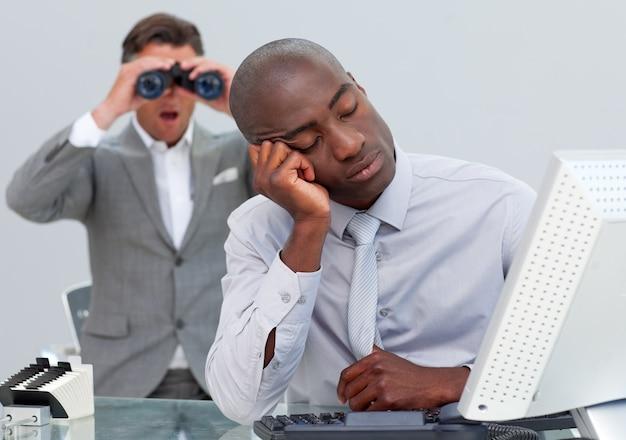 Uomo d'affari addormentato infastidito da un uomo che guarda attraverso il binocolo