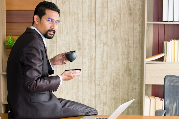 Uomo d'affari adulto che si siede sullo scrittorio e che tiene la tazza di caffè.