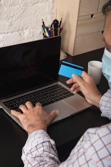 Uomo d'affari adulto con la mascherina chirurgica protettiva, la carta di credito e l'utilizzo del computer portatile che effettua un acquisto online da casa. acquisti online.