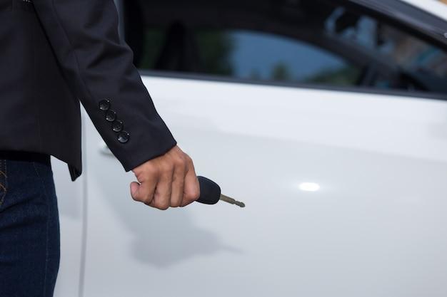 Uomo d'affari adulto maschio in un vestito e in possesso di un tasto auto in mano. auto bianche sullo sfondo