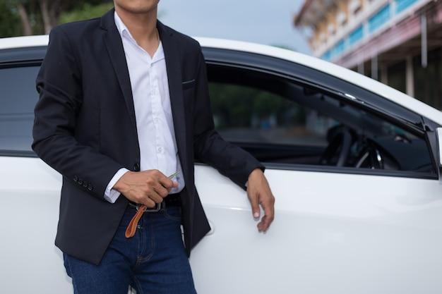 Uomo d'affari adulto maschio in un vestito e in possesso di un tasto auto in mano