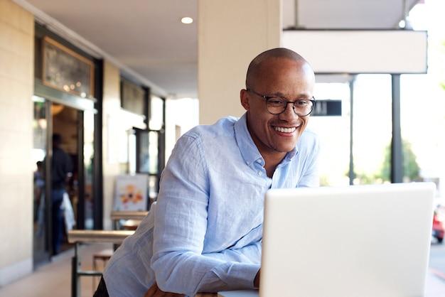 Uomo d'affari africano bello che lavora con il computer portatile