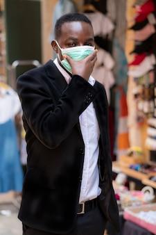 Uomo d'affari africano con maschera medica per proteggere da virus corona o covid-19