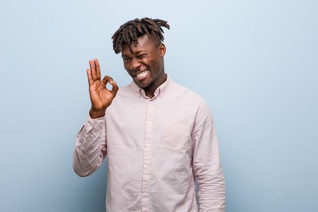 Uomo d'affari africano giovane nero strizza l'occhio e tiene un gesto ok con la mano.