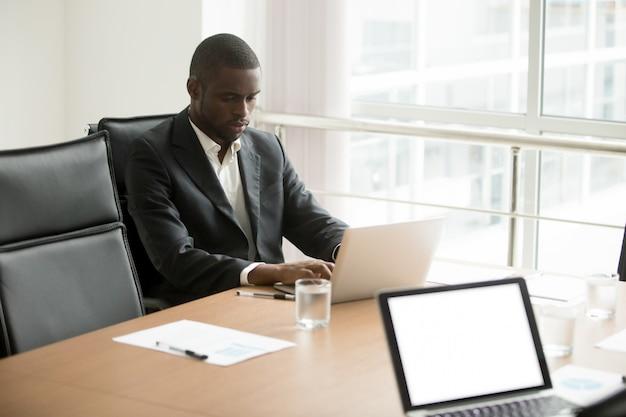 Uomo d'affari africano serio che lavora al computer portatile che si siede al tavolo da conferenza