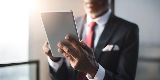 Uomo d'affari africano using digital tablet concept
