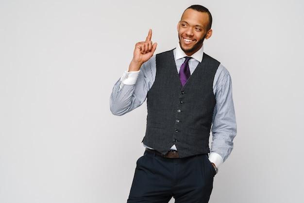 Uomo d'affari afro-americano che si presenta con il dito su grigio.