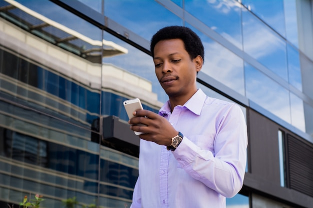 Uomo d'affari afro che per mezzo del suo telefono cellulare.