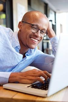 Uomo d'affari afroamericano che lavora al computer portatile