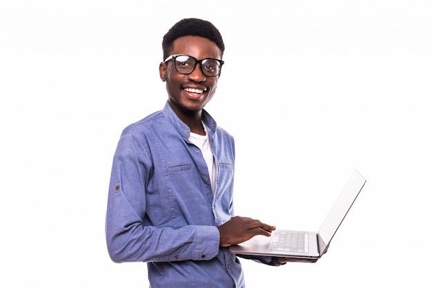 Uomo d'affari afroamericano che per mezzo di un computer portatile e una posa isolati sopra la parete bianca