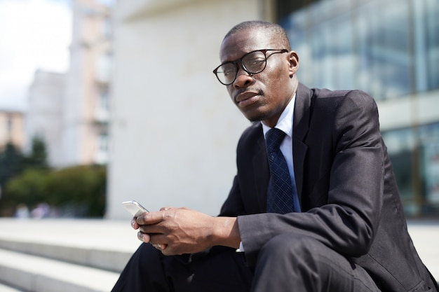 Uomo d'affari afroamericano che si siede sui punti
