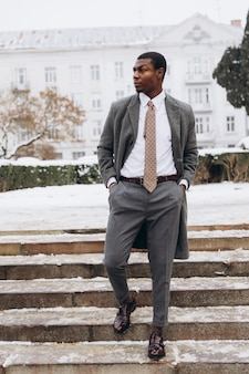 Uomo d'affari afroamericano che utilizza smartphone nella via nevosa della città di inverno