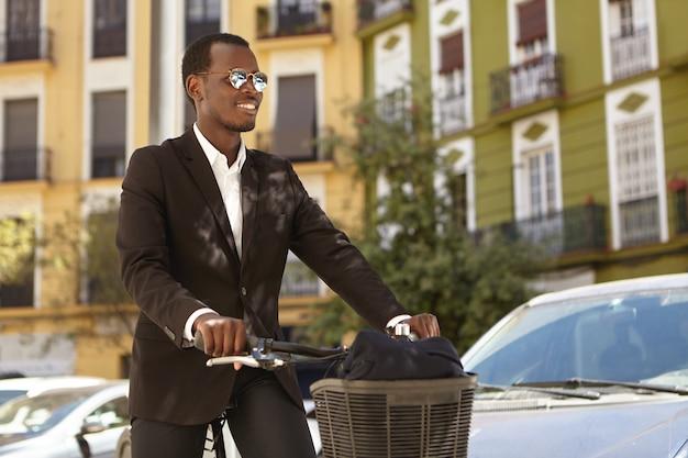 Uomo d'affari afroamericano ecologico felice di successo attraente in abbigliamento formale godendo il giro in città sulla sua bicicletta retrò, in bicicletta a casa dopo una giornata di lavoro in ufficio, rilassato e spensierato