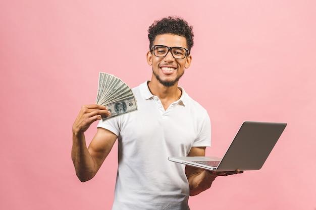 Uomo d'affari afroamericano fare soldi da internet, tenendo in mano contanti e laptop in un altro
