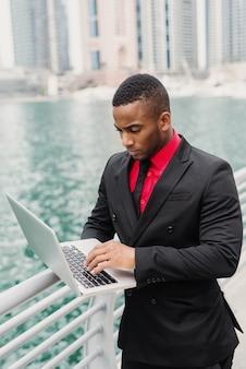 Uomo d'affari afroamericano occupato che sta nel porto e che guarda attraverso alcuni documenti sul suo computer portatile.