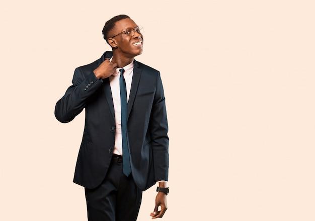 Uomo d'affari afroamericano sentirsi stressato, ansioso, stanco e frustrato, tirando il collo della camicia, sembrando frustrato dal problema contro la parete beige
