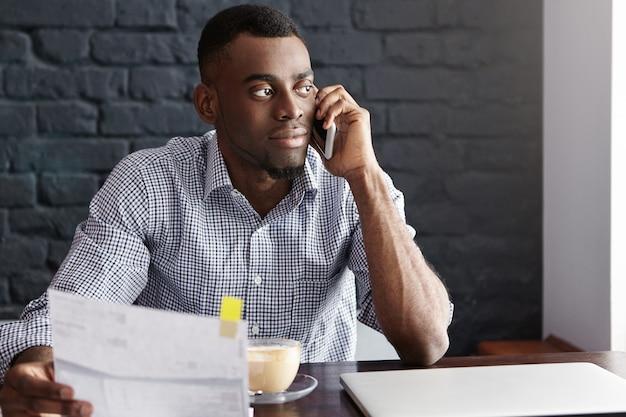 Uomo d'affari afroamericano sicuro bello che fa lavoro di ufficio